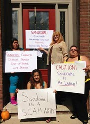 Group with signs saying Sandoval is a scam artist at his front door