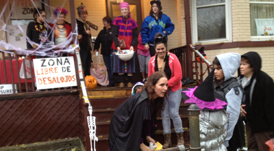 People on the front porch with Halloween decorations, costumes, candy and anti-eviction sign