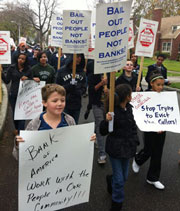 Marchers hold signs protesting Bank of America plan to evict Cullors family
