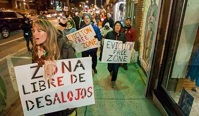 People marching on a commercial street with signs: Zona Libre de Desalojos; and Eviction-free Zone.