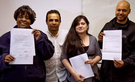 Four people holding copies of their deeds