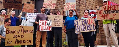 Group of people with anti-eviction signs in front of the bank branch