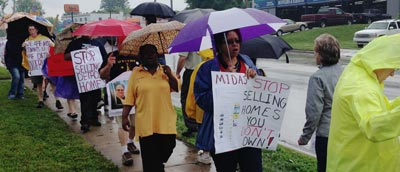 Group marches with signs telling Midas to stop selling homes you don't own