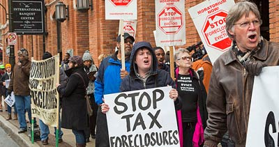 Group marching outside building with signs: stop tax foreclosures