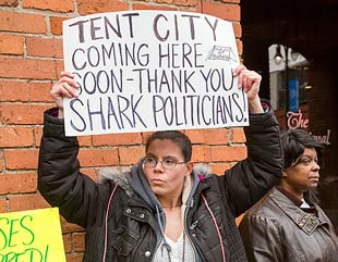 Woman holding sign: TENT CITY coming here soon - thank you shark politicians