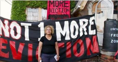 Jennette standing in front of home with sign- Not One More Eviction
