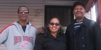 Three family members standing in front of home